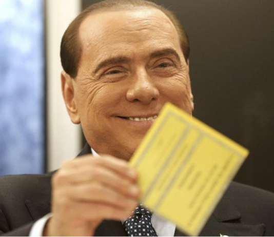 """Silvio Berlusconi, visibilmente attizzato, mostra la scheda alla Femen in topless e si prepara a dirle: """"La vedi questa?..."""""""