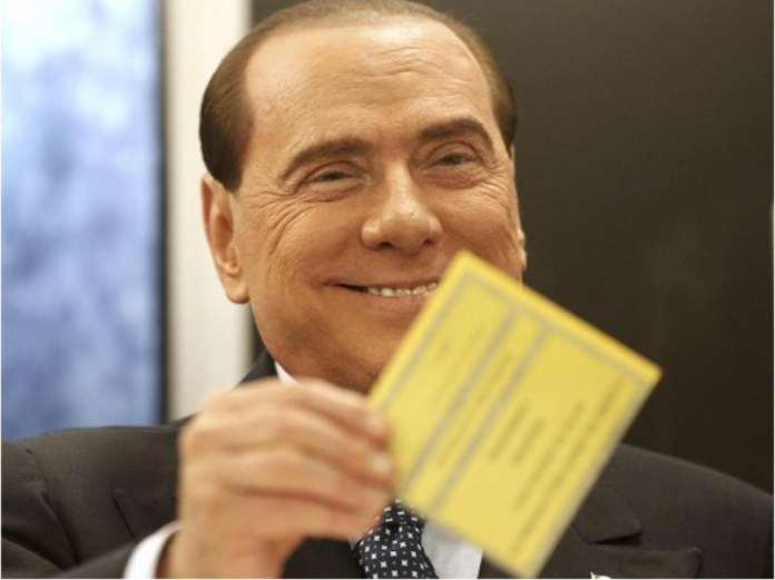 Silvio Berlusconi, visibilmente attizzato, mostra la scheda alla Femen in topless e si prepara a dirle: